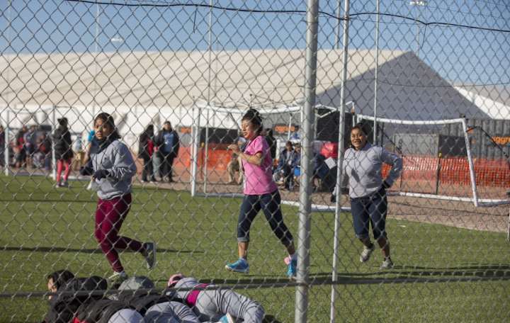 CORRECTS TO CLARIFY TEENS WERE JUST RUNNING AND NOT LOOKING AT PROTESTERS, AS THERE WERE NO PROTESTS THAT DAY - In this Nov. 25, 2018 photo provided by Ivan Pierre Aguirre, migrant teens held inside the Tornillo detention camp run at the facility in Tornillo, Texas. The Trump administration announced in June 2018 that it would open the temporary shelter for up to 360 migrant children in this isolated corner of the Texas desert. Less than six months later, the facility has expanded into a detention camp holding thousands of teenagers - and it shows every sign of becoming more permanent. (Ivan Pierre Aguirre via AP)