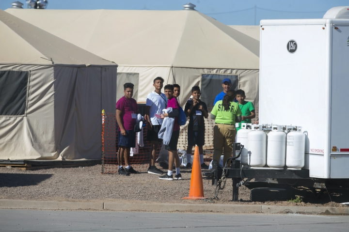 In this Nov. 15, 2018 photo provided by Ivan Pierre Aguirre, migrant teens held inside the Tornillo detention camp look at protestors waving at them outside the fences surrounding the facility in Tornillo, Texas. The Trump administration announced in June 2018 that it would open the temporary shelter for up to 360 migrant children in this isolated corner of the Texas desert. Less than six months later, the facility has expanded into a detention camp holding thousands of teenagers - and it shows every sign of becoming more permanent. (Ivan Pierre Aguirre via AP)