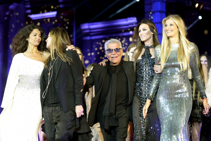 FILE - This Saturday, May 25, 2013 file photo shows Italian fashion designer Roberto Cavalli, center, walking with a group of models on stage during the opening ceremony of the 21st Life Ball in front of city hall in Vienna, Austria. The Roberto Cavalli fashion house is looking for future growth in the home décor and furniture sector, with a new project furnishing a luxury residential building in Bahrain. (AP Photo/Hans Punz, File )