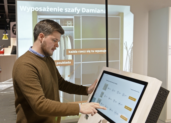 In this Thursday Nov. 22, 2018 photo, Andreas Flygare, the project manager for the new Warsaw Ikea store presents a system projecting furniture interior a wall, in Warsaw, Poland. The new Ikea store, recently opened in a city shopping mall, is part of a global strategy by the Swedish furniture chain to adapt to a changing consumer environment by opening small, accessible stores in city centers to complement the traditional large out-of-town store stores. (AP Photo/Alik Keplicz)