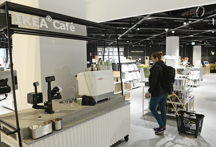 In this Thursday Nov. 22, 2018 photo, a customer walks in a new Ikea store, in Warsaw, Poland. The store, recently opened in a city shopping mall, is part of a global strategy by the Swedish furniture chain to adapt to a changing consumer environment by opening small, accessible stores in city centers to complement the traditional large out-of-town store stores. (AP Photo/Alik Keplicz)