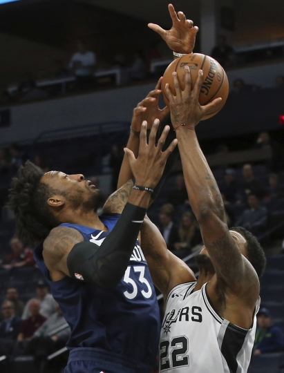 San Antonio Spurs' Rudy Gay, right, tries to control the ball as Minnesota Timberwolves' Robert Covington defends in the first half of an NBA basketball game Wednesday, Nov. 28, 2018, in Minneapolis. (AP Photo/Jim Mone)