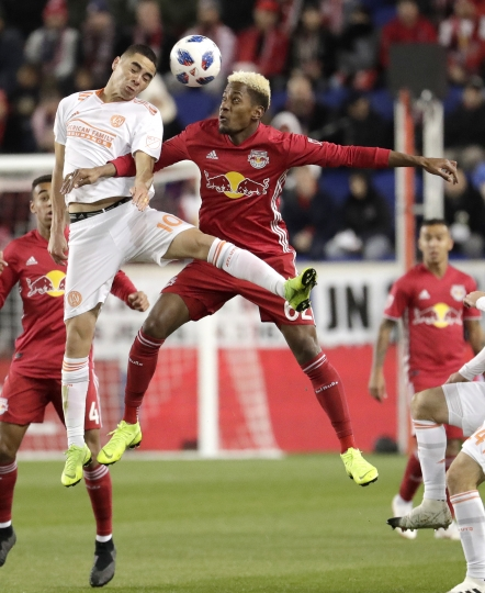 Atlanta United midfielder Miguel Almiron, left, and New York Red Bulls midfielder Tyler Adams go up for the ball during the first half of the second leg of the MLS soccer Eastern Conference championship Thursday, Nov. 29, 2018, in Harrison, N.J. (AP Photo/Julio Cortez)