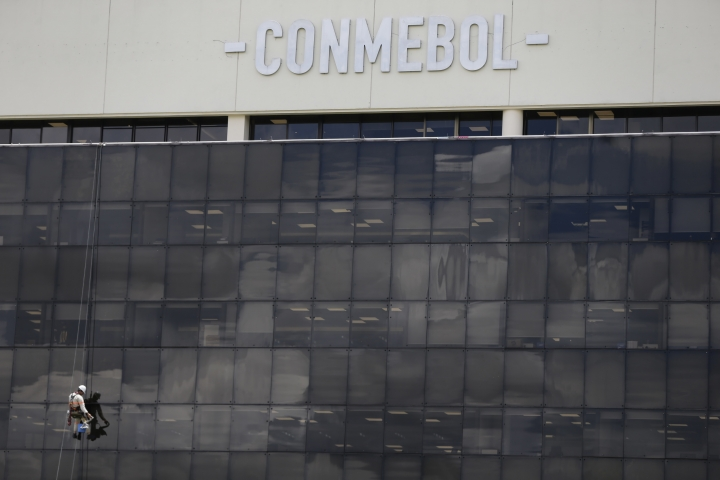 A worker cleans the windows at CONMEBOL headquarters in Luque, Paraguay, Thursday, Nov. 29, 2018. Inside, soccer authorities are discussing what venue will host the final Copa Libertadores match between Boca Juniors and River Plate of Argentina, after it was suspended twice in Buenos Aires, Argentina. (AP Photo/Jorge Saenz)
