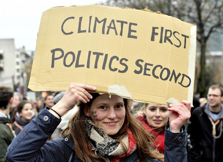 A demonstrator holds a placard which reads 'climate first, politics second' during a 'Claim the Climate' march in Brussels, Sunday, Dec. 2, 2018. The climate change conference, COP24, will take place in Poland from Dec. 2-14. (AP Photo/Geert Vanden Wijngaert)