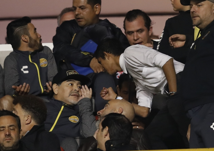 Dorados head coach Diego Maradona, left center, talks with a man prior to the final leg of Mexico's second division soccer league against Atletico San Luis in San Luis Potosi, Mexico, Sunday, Dec. 2, 2018. Maradona was sent off the field during the first leg of the final after receiving a red card. (AP Photo/Eduardo Verdugo)