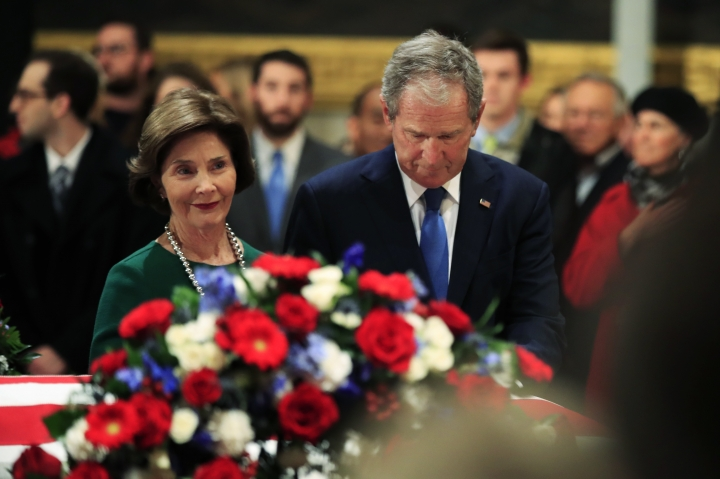 Former President George W. Bush and former first lady Laura Bush pay their respect to his father former President George H.W. Bush as he lie in state at the U.S. Capitol in Washington, Tuesday, Dec. 4, 2018. (AP Photo/Manuel Balce Ceneta)