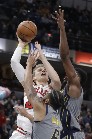 Chicago Bulls' Lauri Markkanen puts up a shot against Indiana Pacers' Cory Joseph (6) and Thaddeus Young during the second half of an NBA basketball game, Tuesday, Dec. 4, 2018, in Indianapolis. Indiana won 96-90. (AP Photo/Darron Cummings)
