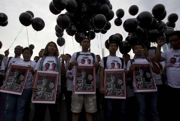 Activists holding signs with the Time Magazine cover showing wives of two Reuters journalists stand during a rally to mark one year anniversary of their arrest, Wednesday, Dec. 12, 2018, in front of city hall in Yangon, Myanmar. (AP Photo/Thein Zaw)
