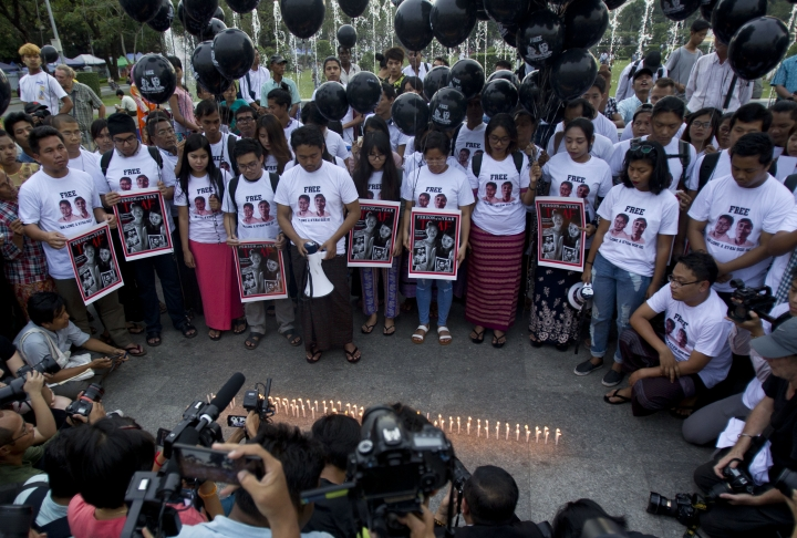 Activists holding signs with the Time Magazine cover with wives of two Reuters journalists stand to pray during a rally to mark one year anniversary of their arrest, Wednesday, Dec. 12, 2018, in front of city hall in Yangon, Myanmar. (AP Photo/Thein Zaw)