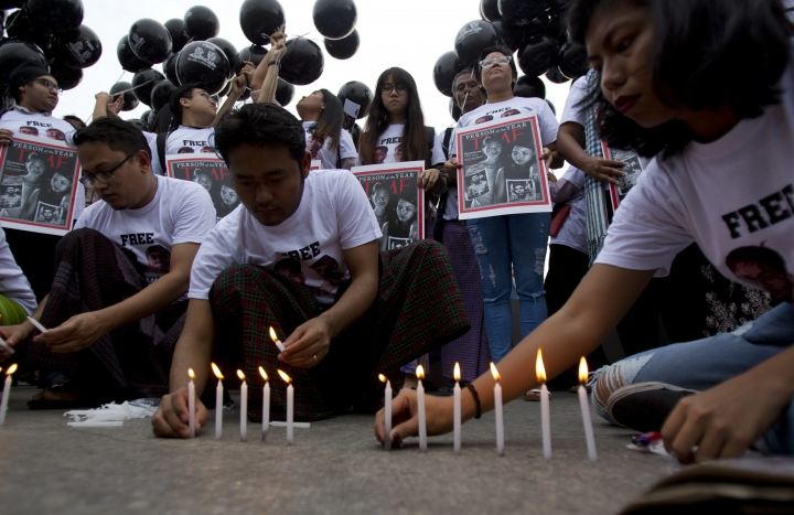 Activists light candles while others hold signs with the Time Magazine cover with wives of two Reuters journalists stand during a rally to mark one year anniversary of their arrest, Wednesday, Dec. 12, 2018, in front of city hall in Yangon, Myanmar. (AP Photo/Thein Zaw)