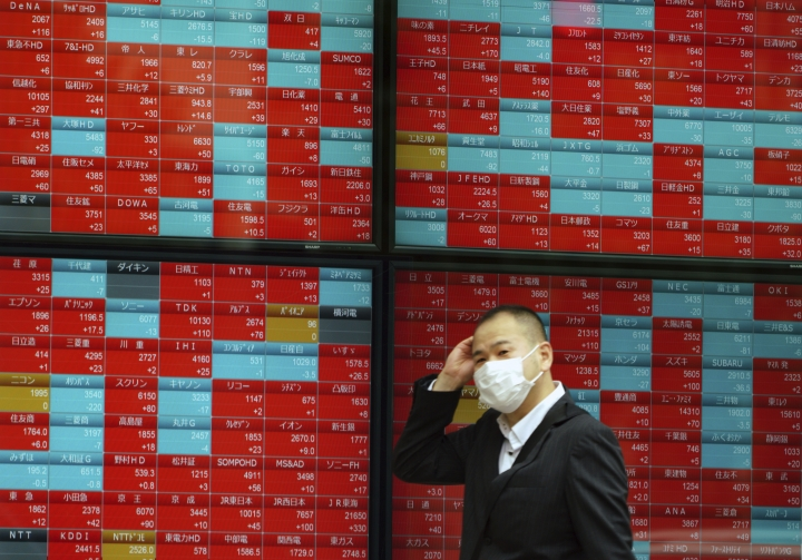 In this Nov. 7, 2018, photo, a man walks past an electronic stock board showing Japan's Nikkei 225 index at a securities firm in Tokyo. Asian markets tumbled on Friday, Dec. 14, 2018 after China reported weaker-than-expected economic data, stirring up worries about the state of the world's second largest economy. (AP Photo/Eugene Hoshiko)