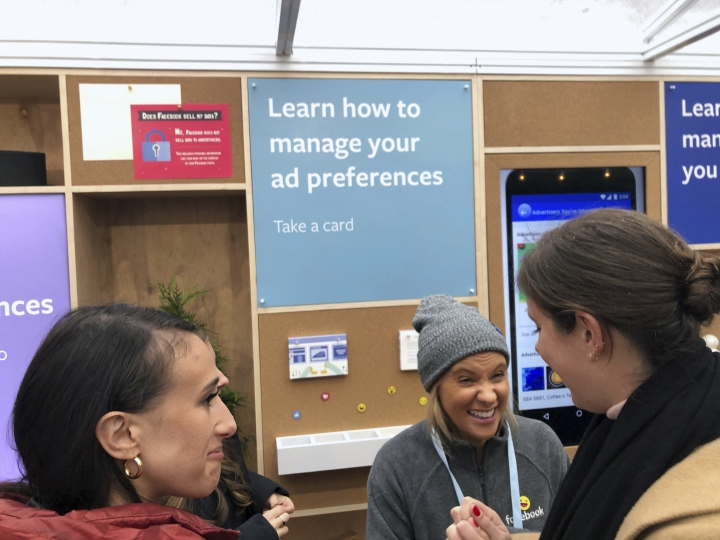 "People talk inside a Facebook ""pop-up"" trailer in New York's Bryan Park on Thursday, Dec. 13, 2018. The company hosted a one-day event open to the public, with Facebook employees on hand to answer questions about privacy settings and other issues. The pop-up event caps a difficult year for the company.(AP Photo/Barbara Ortutay)"