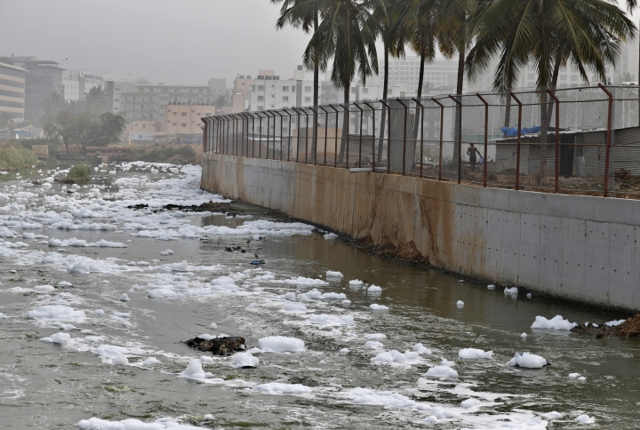 In this Monday, Dec. 10, 2018 photo toxic froth from industrial pollution floats on Bellundur Lake in Bangalore, India. As politicians haggle at a U.N. climate conference in Poland over ways to limit global warming, the industries and machines powering our modern world keep spewing their pollution into the air and water. The fossil fuels extracted from beneath the earth's crust _ coal, oil and gas _ are transformed into the carbon dioxide that is now heating the earth faster than scientists had expected even a few years ago. (AP Photo/Aijaz Rahi)