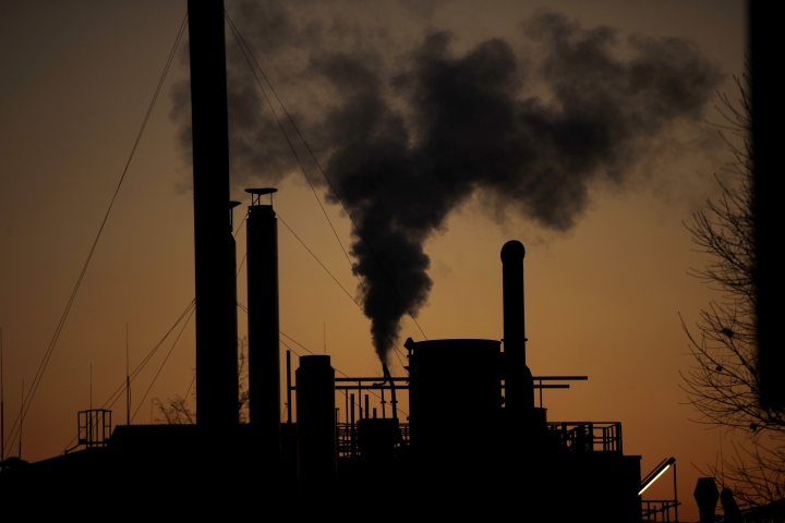 Smoke billows from a chimney of the Solvay factory for production and processing of plastic materials, in Ospiate, near Milan, Italy, Friday, Dec. 14, 2018. The climate change conference, COP24, is closing today in Katowice, Poland. (AP Photo/Luca Bruno)