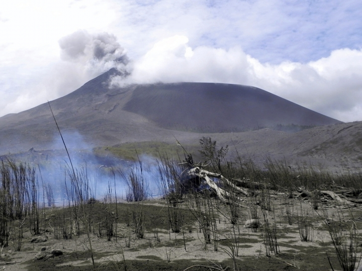 FILE - In this July 3, 2011, file photo, shows Mount Soputan seen from Tombatu village in North Sulawesi, Indonesia. Mount Soputan, located on the northern part of Sulawesi island, erupted twice Sunday morning, Dec. 16, 2018, according to the national disaster agency's spokesman, Sutopo Purwo Nugroho. (AP Photo/Grace Wakary, File)