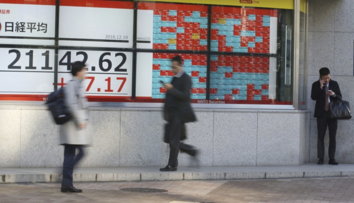 People walk by an electronic stock board of a securities firm in Tokyo, Wednesday, Dec. 19, 2018. Asian stocks were mixed on Wednesday, as traders mulled over the Federal Reserve's interest rate decision and weaker-than-expected Japanese trade data.(AP Photo/Koji Sasahara)