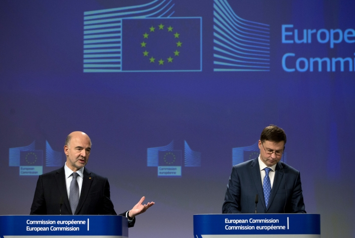 European Commissioner for Economic and Financial Affairs Pierre Moscovici, left, and European Commissioner for Euro and Social Dialogue Valdis Dombrovkis participate in a media conference at EU headquarters in Brussels, Wednesday, Dec. 19, 2018. The European Commission says it has reached an agreement with Italy to avert action over the country's budget plans, which the EU's executive arm had warned could break euro currency rules. (AP Photo/Virginia Mayo)