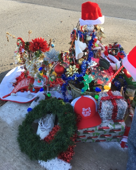 In this Dec. 18, 2018 photo, Christmas decorations and donations surround what's now known as the Christmas weed in Toledo, Ohio. The street corner weed has become a holiday attraction and a source of goodwill in the city. (AP Photo/John Seewer)