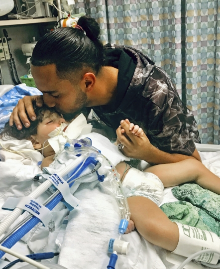 This recent but undated photo, released Monday, Dec. 17, 2018, by the Council on American-Islamic Relations in Sacramento, Calif., shows Ali Hassan kissing his dying 2-year-old son Abdullah in a Sacramento hospital. The boy's Yemeni mother, blocked by the Trump administration's travel ban, has won her fight for a waiver that would allow her to travel to California to see her son. Basim Elkarra of the Council on American-Islamic Relations in Sacramento, Calif., said Shaima Swileh was granted a visa Tuesday, Dec. 18, 2018, and will be flying to San Francisco on Wednesday, Dec. 19, 2018. (Council on American-Islamic Relations via AP)