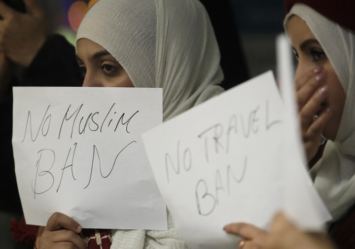 Supporters of Shaima Swileh hold up signs as they await her arrival at San Francisco International Airport in San Francisco, Wednesday, Dec. 19, 2018. Swileh is the Yemeni mother who won her fight for a waiver from the Trump administration's travel ban that would allow her to go to California to see her dying 2-year-old son. (AP Photo/Jeff Chiu)
