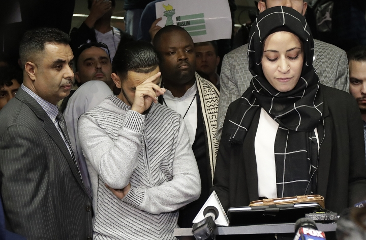 Ali Hassan, center left, listens to speakers at a news conference after his wife Shaima Swileh, hidden, arrived at San Francisco International Airport in San Francisco, Wednesday, Dec. 19, 2018. Swileh is the Yemeni mother who won her fight for a waiver from the Trump administration's travel ban that would allow her to go to California to see her dying 2-year-old son. (AP Photo/Jeff Chiu)