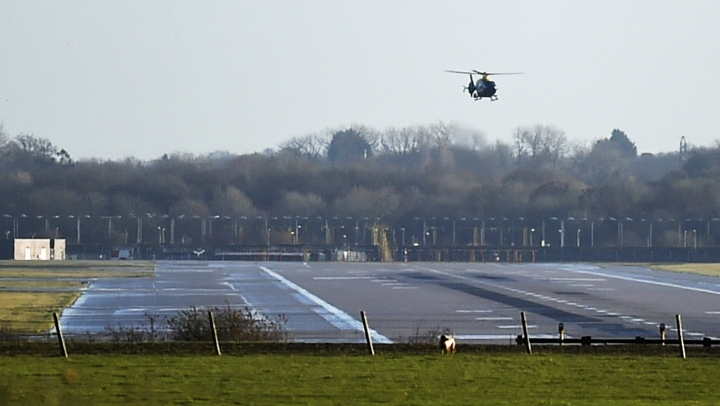 A police helicopter flies over the runway at Gatwick airport, London, as the airport remains closed with incoming flights delayed or diverted to other airports, after drones were spotted over the airfield last night and this morning Thursday Dec. 20, 2018. London's Gatwick Airport remained shut during the busy holiday period Thursday while police and airport officials investigate reports that drones were flying in the area of the airfield. (Pete Summers/PA via AP)