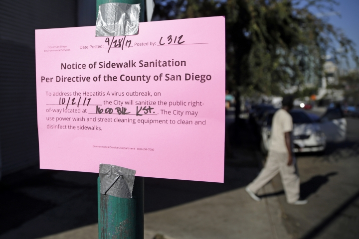 FILE - In this Sept. 28, 2017 file photo a man passes behind a sign warning of an upcoming street cleaning in San Diego. An audit by the California Legislature has found the city and county of San Diego faltered in quickly controlling a Hepatitis A outbreak last year that grew to be among the largest seen in the United States in decades.. (AP Photo/Gregory Bull, File)
