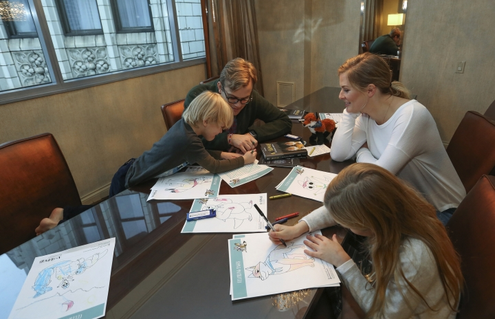 Adam Bryan and Hannah Steadman work with their children Wesley and Greta Rose on puzzles included in complimentary backpacks provided with other incentives by the Wyndham Grand Hotel in Chicago on Dec. 1, 2018. A growing number of hotels are helping guests take a vacation from their vacation by offering incentives to guests willing to lock up their cell phones (AP Photo/Teresa Crawford)