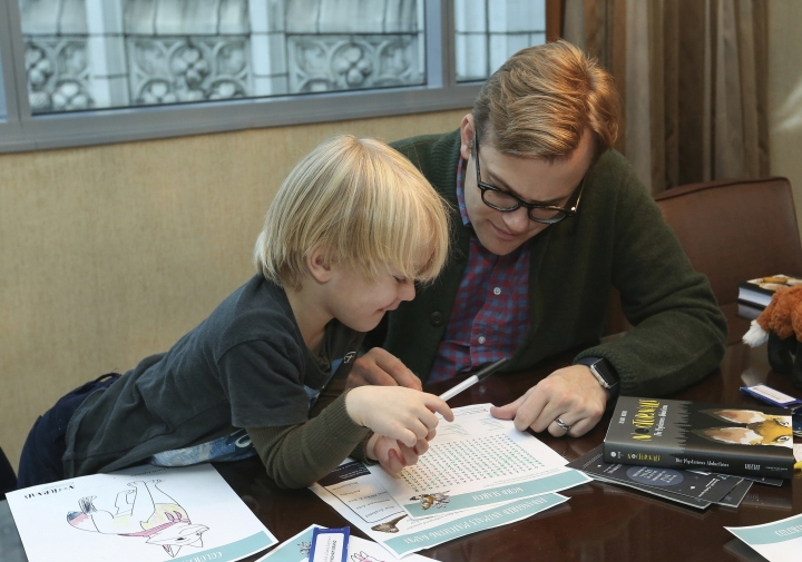 Adam Bryan and his son Wesley work together on puzzles included in complimentary backpacks provided with other incentives by the Wyndham Grand Hotel in Chicago on Dec. 1, 2018. A growing number of hotels are helping guests take a vacation from their vacation by offering incentives to guests willing to lock up their cell phones (AP Photo/Teresa Crawford)