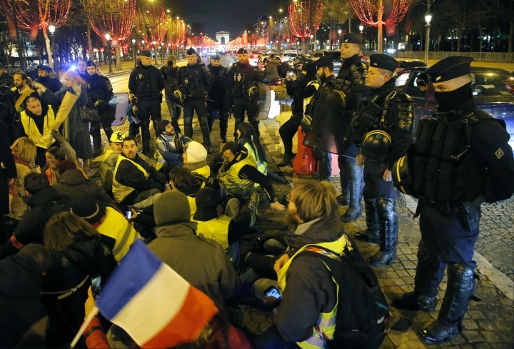 Riot police officers block police officers as they take part in a rally to protest their working condition at the Champs-Elysees avenue in Paris, France, Thursday, Dec. 20, 2018. About 80-100 people protested Thursday in front of a police station near the elegant Champs-Elysees avenue, flashpoint of recent rioting. (AP Photo/Michel Euler)