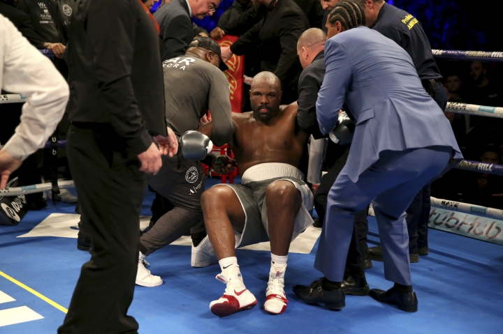 Dereck Chisora is helped up after being knocked out by Dillian Whyte during a heavyweight boxing bout Saturday, Dec. 22, 2018, in London. (Steven Paston/PA via AP)