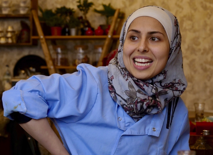 "In this Nov. 9, 2018 photo Malakeh Jazmati smiles in her restaurant in Berlin, Germany. After fleeing her homeland's civil war, Jazmati reinvented herself in Jordan as a TV chef and became known as the ""queen of cooking"" to fellow Syrian refugees. Now in Berlin she's starting over again, opening a restaurant she hopes can serve as ""medicine against homesickness"" for the thousands of newly-arrived Syrians in the German capital. (AP Photo/Jona Kallgren)"