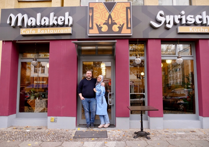 """In this Nov. 9, 2018 photo Malakeh Jazmati and her husband Mohammad Al Ghamian pose outside her restaurant in Berlin, Germany. After fleeing her homeland's civil war, Jazmati reinvented herself in Jordan as a TV chef and became known as the """"queen of cooking"""" to fellow Syrian refugees. Now in Berlin she's starting over again, opening a restaurant she hopes can serve as """"medicine against homesickness"""" for the thousands of newly-arrived Syrians in the German capital. (AP Photo/Jona Kallgren)"""