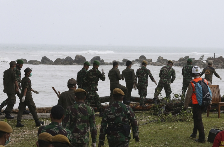 Indonesian soldiers and rescue team search the tsunami victims at a beach resort in Tanjung Lesung, Indonesia, Monday, Dec. 24, 2018. Doctors are working to help survivors and rescuers are looking for more victims from a deadly tsunami that smashed into beachside buildings along an Indonesian strait. The waves that swept terrified people into the sea Saturday night followed an eruption on Anak Krakatau, one of the world's most infamous volcanic islands. (AP Photo/Achmad Ibrahim)