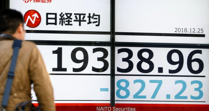 A man looks at Monday's loss of Nikkei stock index on an electronic stock board at a securities firm in Tokyo, Monday, Dec. 25, 2018. President Donald Trump's attacks on the Federal Reserve spooked the stock market on Christmas Eve, and efforts by his Treasury secretary to calm investors' fears only seemed to make matters worse, contributing to another day of heavy losses on Wall Street. (Yohei Fukai/Kyodo News via AP)