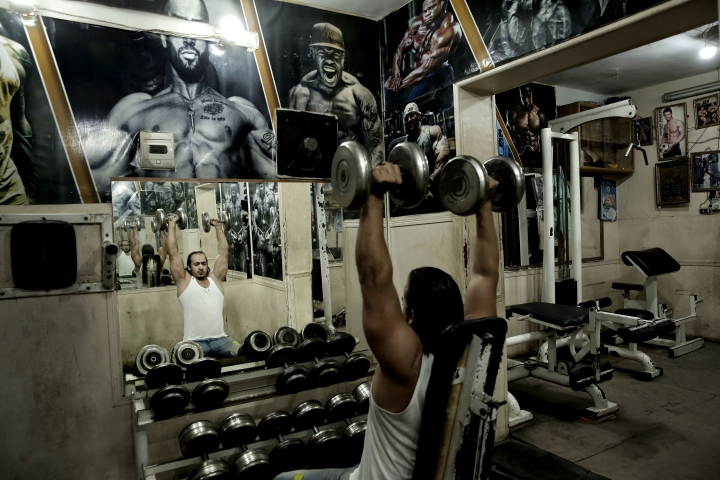 In this Oct. 23, 2018 photo, a man lifts barbells at a gym in the Shubra neighborhood of Cairo, Egypt. In televised comments in December 2018, Abdel-Fattah el-Sissi, the general-turned-president railed about the number of overweight people he sees and told Egyptians they must take better care of themselves. El-Sissi said physical education should become core curriculum at schools and universities and suggested TV shows shouldn't let presenters or guests on the air if they are overweight. (AP Photo/Nariman El-Mofty)