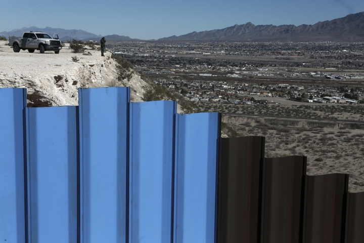FILE - In this Jan. 25, 2017, file photo, an agent from the border patrol, observes near the Mexico-US border fence, on the Mexican side, separating the towns of Anapra, Mexico and Sunland Park, N.M. An 8-year-old boy from Guatemala died in government custody early Tuesday, Dec. 25, 2018, U.S. immigration authorities said. (AP Photo/Christian Torres, File)