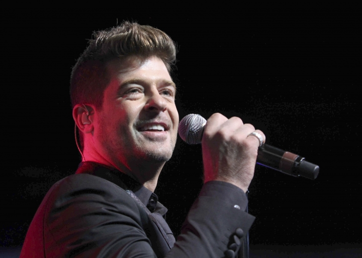 """FILE - In this Aug. 7, 2015, file photo, Robin Thicke performs during the Steve Harvey Morning Show live broadcast at the Georgia World Congress Center in Atlanta. The 41-year-old """"Blurred Lines"""" singer proposed to model April Love Geary with friends and family. She announced the couple's engagement in an Instagram post Monday, Dec. 24, 2018, as a video shows Thicke asking the 24-year-old Geary to marry him and her writing """"YES YES 1000xYES."""" (Photo by Robb D. Cohen/Invision/AP, File)"""