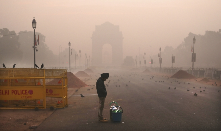 In this Wednesday, Dec. 26, 2018, photo, a boy selling tea awaits customers early morning amidst smog in New Delhi, India. Authorities have ordered fire services to sprinkle water from high rise building to settle dust particles and stop burning of garbage and building activity in the Indian capital as the air quality hovered between severe and very poor this week posing a serious health hazard for millions of people. (AP Photo/Manish Swarup)