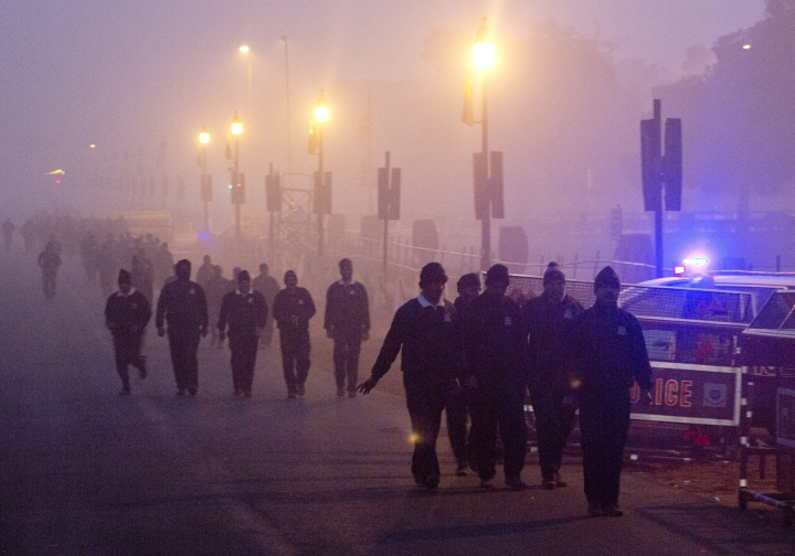 In this Wednesday, Dec. 26, 2018, photo, Indian military personals walk amidst morning smog in New Delhi, India. Authorities have ordered fire services to sprinkle water from high rise building to settle dust particles and stop burning of garbage and building activity in the Indian capital as the air quality hovered between severe and very poor this week posing a serious health hazard for millions of people. (AP Photo/Manish Swarup)