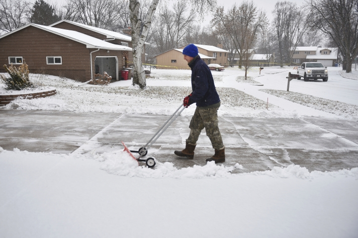 In this Wednesday, Dec. 26, 2018 photo, Lance Nieuwenhuis shovels snow out of his driveway in Sioux Falls, S.D. The weather service in Sioux Falls, South Dakota says rain is changing over to snow from west to east Thursday with heavy snow and gusty winds through Friday. (Briana Sanchez/The Argus Leader via AP)