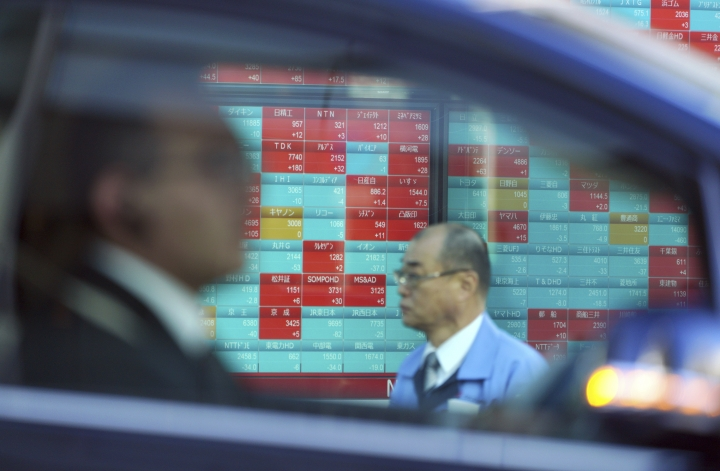 A man walks as a car drives by past an electronic stock board showing Japan's Nikkei 225 index at a securities firm in Tokyo Friday, Dec. 28, 2018. Most Asian stock markets gained while Japan edged down following Wall Street's rally at the end of a turbulent week. (AP Photo/Eugene Hoshiko)