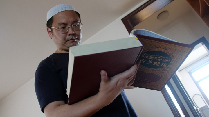 In this Sept. 28, 2018, photo, Muslim Chinese poet Cui Haoxin reads an Arabic prayer from a Quran in his home in the city of Jinan in China's eastern province of Shandong. Cui is an outspoken critic of the government's policies towards Muslims at home and abroad, writing poetry and tweeting about alleged abuses against Islamic traditions. (AP Photo/Sam McNeil)