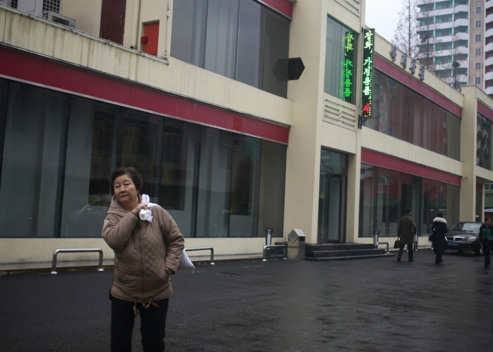 """In this Dec. 21, 2018, photo, a North Korean woman walks outside Bugsae Shop, also known as the """"Singapore Shop,"""" in Pyongyang, North Korea. Despite the unwanted publicity of a criminal trial for one of their main suppliers, business is booming at Pyongyang's """"Singapore shops,"""" which sell everything from Ukrainian vodka to brand-name knock-offs from China. The stores stock many of the very things United Nations' sanctions banning trade in luxury goods are intended to block and provide a nagging reminder that not all potential trade partners are lining up behind the U.N.'s pronouncements or the Trump administration's policy of maximum pressure on the North. Especially when there's a buck, or a few million bucks, to be made. (AP Photo/Dita Alangkara)"""