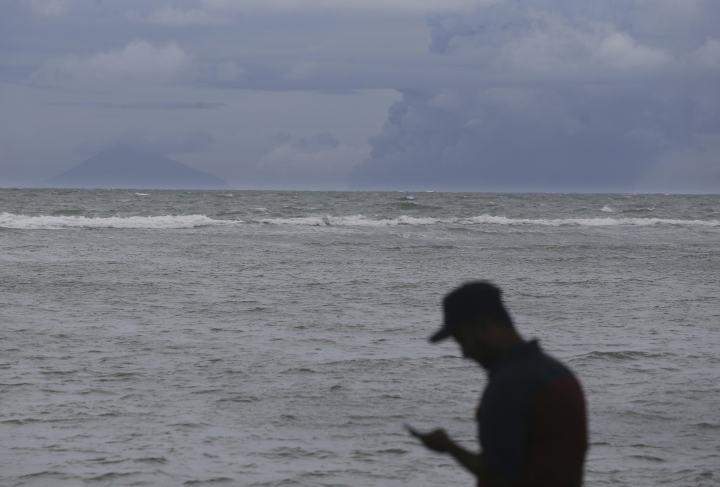 A man look a mobile phone as Anak Krakatau, right, is seen on the horizon off Carita beach, Indonesia, Friday, Dec. 28, 2018. Indonesia raised the danger level for an island volcano that triggered a tsunami on the weekend, killing at least 430 people in Sumatra and Java, and widened its no-go zone.(AP Photo/Achmad Ibrahim)