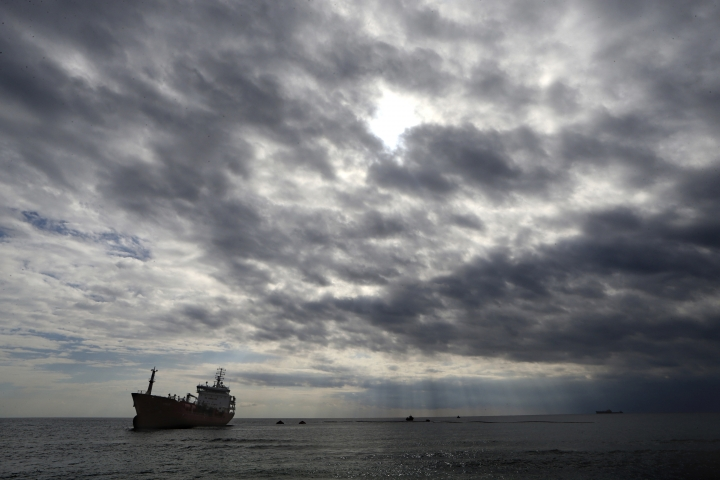 The Athlos tanker lays aground about 200-yards from the village of Zygi off the south coast of Cyprus, Saturday, Dec. 29, 2018. Cyprus authorities say five crew members who jumped overboard to avoid a fire aboard the Maltese-flagged oil tanker, have been rescued and taken to hospital. (AP Photo/Petros Karadjias)