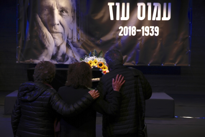 People show respect pass by the coffin of Amos Oz during his funeral service in Tel Aviv, Israel, Monday, Dec. 31, 2018. Israeli author Amos Oz, one of the country's most widely acclaimed writers and a pre-eminent voice in its embattled peace movement, died on Friday after a battle with cancer, his family announced. He was 79. (AP Photo/Ariel Schalit)