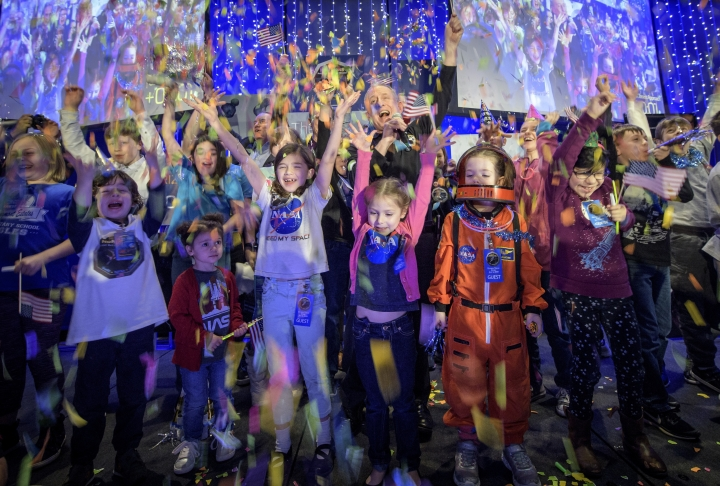 In this photo provided by NASA, New Horizons principal investigator Alan Stern, of the Southwest Research Institute in Boulder, Colo., center, celebrates with school children at the exact moment that the New Horizons spacecraft made the closest approach of Kuiper Belt object Ultima Thule, early Tuesday, Jan. 1, 2019, at Johns Hopkins University Applied Physics Laboratory in Laurel, Md. (Bill Ingalls/NASA via AP)