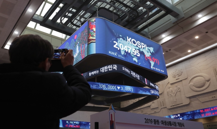 A man takes a photo of screens showing the Korea Composite Stock Price Index (KOSPI) at the Korea Exchange in Seoul, South Korea, Wednesday, Jan. 2, 2019. Asian stock markets have fallen as trading began for 2019 after Chinese factory activity weakened. Benchmarks in Shanghai, Seoul and Hong Kong all declined, while Tokyo was closed. (AP Photo/Lee Jin-man)